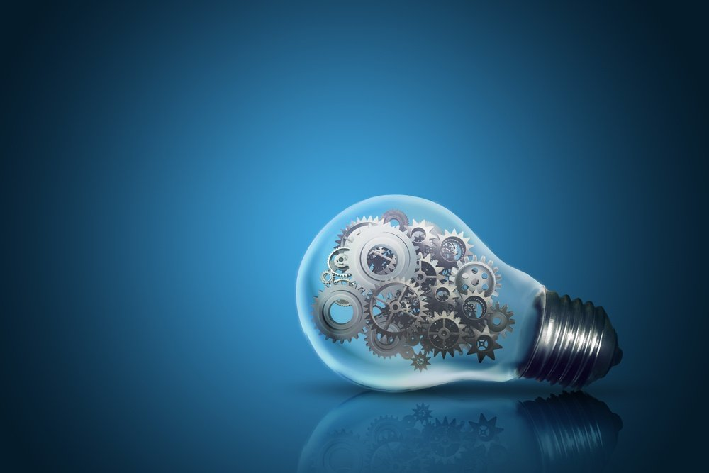 Close up of light bulb with gear mechanism inside isolated on dark blue background.jpeg